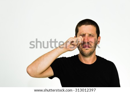 close-up of young caucasian man crying - isolated on white background with copyspace - stock photo