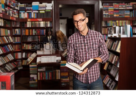 close-up of young caucasian man with eyeglasses in a bookstore with an opened book in his hands smiling, with other bookshelves in background - stock photo