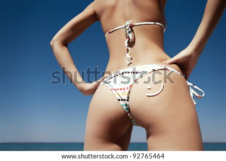 close up of young Caucasian woman's back at the beach with sun lotion applied as smiley symbol - stock photo