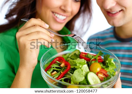 Close-up of young couple eating vegetable salad from glass bowl - stock photo
