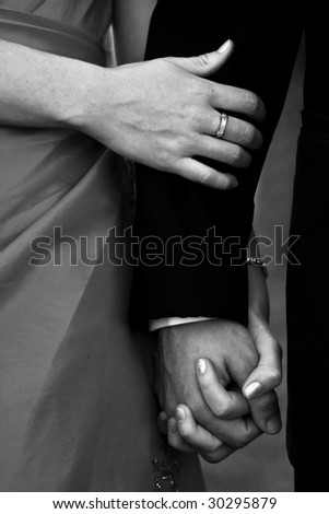 Close up of young couple holding hands - stock photo