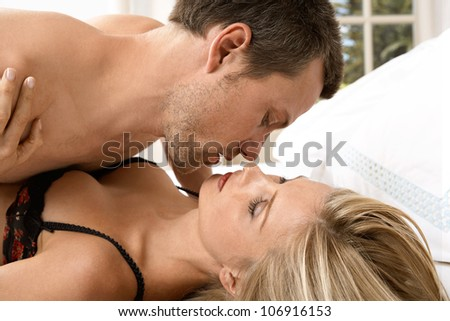 Close up of young couple hugging and kissing in bedroom. - stock photo