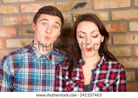 Close Up of Young Couple Puckering Lips and Standing in front of Brick Wall - stock photo