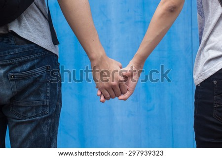 Close up of young couple teenagers in love  holding hands together over blurred blue backgrounds. passion in love concept.selective focused:traveler concept. - stock photo