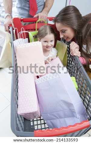 Close-up of young daughter in trolley being pushed by father and mother - stock photo