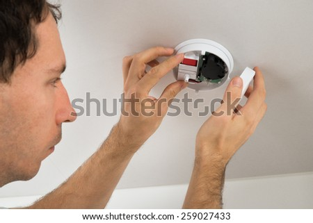 Close-up Of Young Electrician Repairing Smoke Detector - stock photo