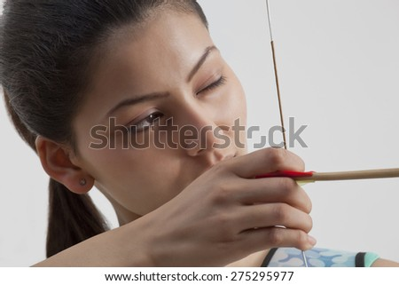 Close-up of young female archer practicing archery against gray background - stock photo
