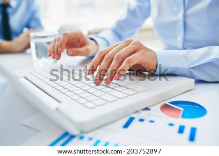 Close-up of young female hands pressing laptop buttons - stock photo
