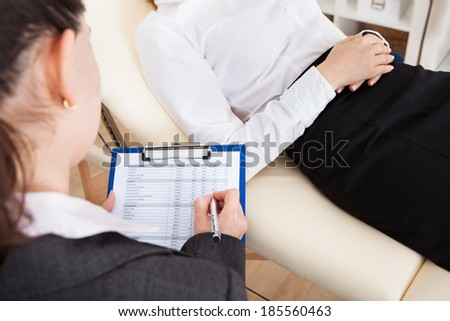 Close-up Of Young Female Psychiatrist Writing On Clipboard - stock photo