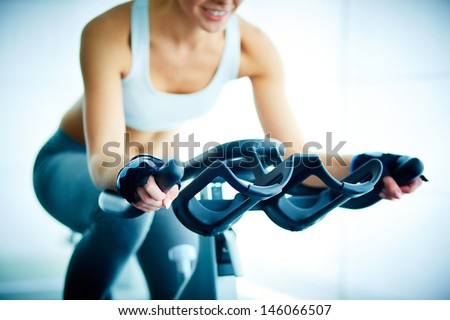 Close-up of young female training on simulator in gym - stock photo