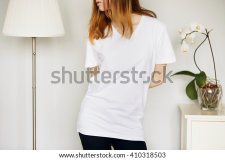 Close up of young female wearing white T-shirt with blank space for your text message, looking away with hands behind her back, cute Caucasian teenage redhead girl posing against gray concrete wall  - stock photo