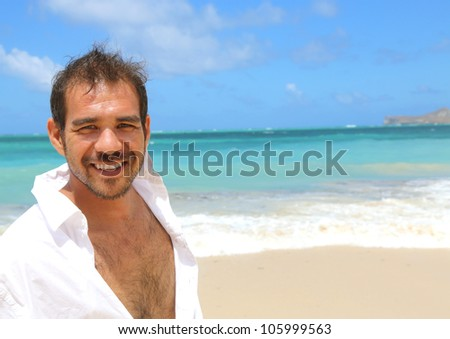 close up of young handsome man smiling standing by beach - stock photo