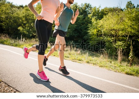 Close up of young man and woman jogging together in park on summer sunny day - stock photo