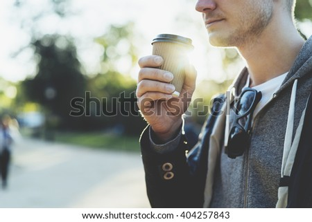 Close-up of young man holding coffee to take away at early morning in sunny park, sunlight, blurred background - stock photo