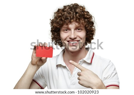 Close up of young man pointing to the blank card he is holding, isolated on white background - stock photo