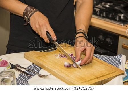 Close up of Young Man's hands Chopping Red Onion with Sharp Knife in Kitchen - Close Up of Man Cooking in Kitchen of First Apartment - stock photo