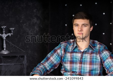 Close Up of Young Man Sitting in Plush Black High Back Chair in Haunted House Setting - stock photo