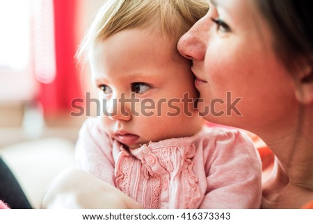 Close up of young mother holding her cute baby daughter, kissing her - stock photo