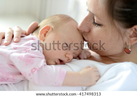 Close up of young mother holding her cute baby daughter lying on her, sleeping, kissing her - stock photo