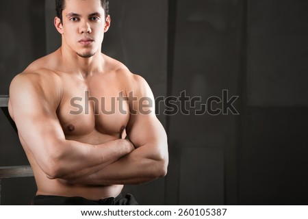 Close up of young muscular man lifting weights over dark background - stock photo