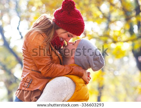 Close up of young romantic couple on a sunny autumn day in the park. They express tenderness. - stock photo