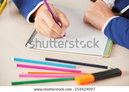 Close up of young school girl with pencils writing while sitting in school desk - stock photo
