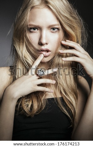 Close-up of young sexy woman with long blonde hair, jewelry, fashionable hairstyle and natural make-up, looking at camera - stock photo