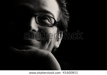 Close-up of young smiling man resting chin on palm looking upwards, low key, black and white - stock photo