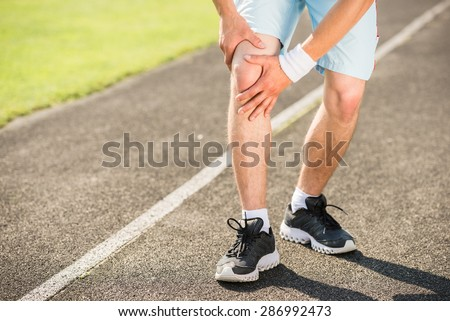 Close-up of young sporty man prepares to run sprint. - stock photo
