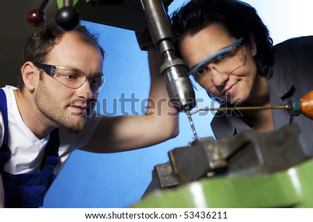 Close-up of young technicians in blue and grey overall working on pillar drilling machine in workshop, blue background, focus on people. - stock photo