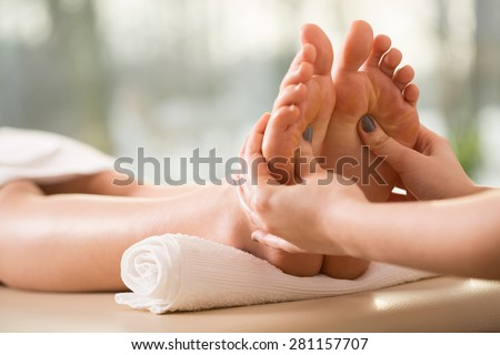 Close-up of young woman having reflexology - stock photo