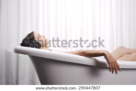 Close up of young woman lying in a bathtub listening to music with big headphones on her head. Concept of relaxation and freedom. - stock photo