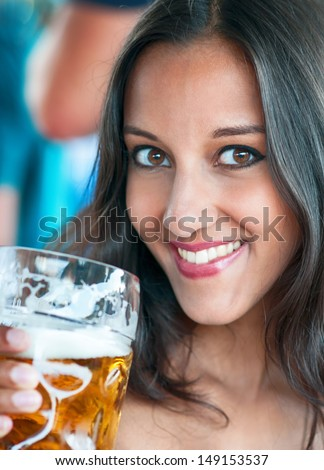 Close-up of young woman with a glass of beer - stock photo