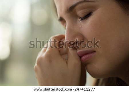 Close-up of young woman with problems crying - stock photo