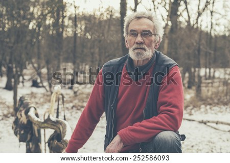 Close up Old Active Man in Casual Jacket Looking Afar Seriously at the Snowed Forest - stock photo