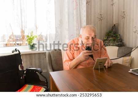 Close up Old Bald Man Cleaning his Beard with Electric Razor at the Table in the Living Room with Small Rectangular Mirror. - stock photo