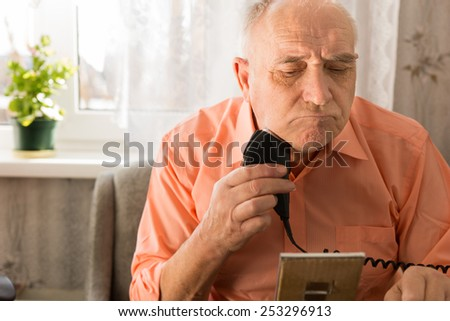 Close up Old Man Shaving Beard with Electric Razor Seriously in Front Small Mirror - stock photo