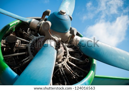 Close up on a big old, green airplane (biplane) engine with enormous propeller. Pre-focused on engine parts. - stock photo