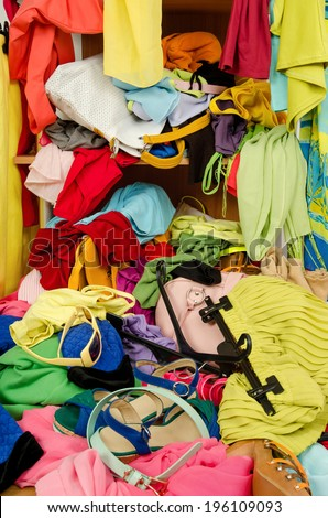 Close up on a big pile of clothes and accessories thrown on the ground. Untidy cluttered wardrobe with colorful clothes and accessories falling out of a shelf. - stock photo