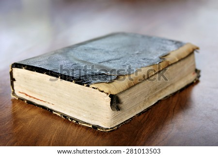 Close up on a black leather bound tattered and torn old vintage book, the Holy Bible sitting on Wooden Table.  Shallow depth of field. - stock photo