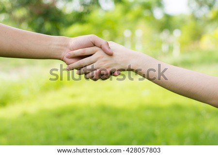 Close up on a man and a woman holding hands at green background,Hand help and hope concept,helping hand - stock photo