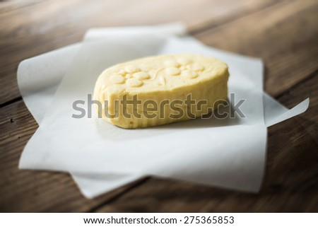 close up on a mound of rustic butter wrapped in paper placed on a wooden table - stock photo
