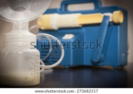 Close up on a old breast pump with a bottle filled with breast milk .A breast pump is a mechanical device that extracts milk from the breasts of a lactating woman. - stock photo