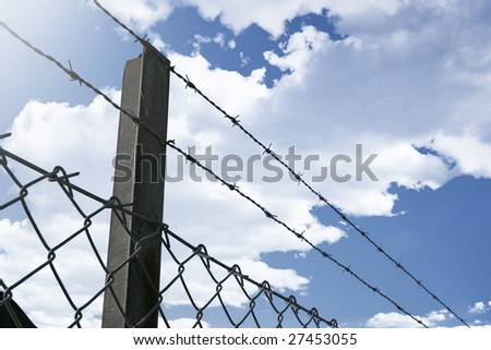 Close up on a security fence with barb wire. - stock photo
