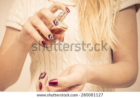close up on a woman spraying perfume on her arm. concept about cosmetics and beauty - stock photo