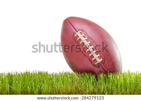 Close-up on an American football on a grass surface isolated on white background - stock photo