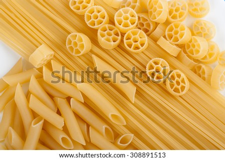 Close up on assortment of uncooked pasta on a white background - stock photo