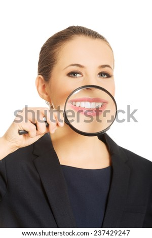 Close up on business woman's teeth through magnyfying glass. - stock photo