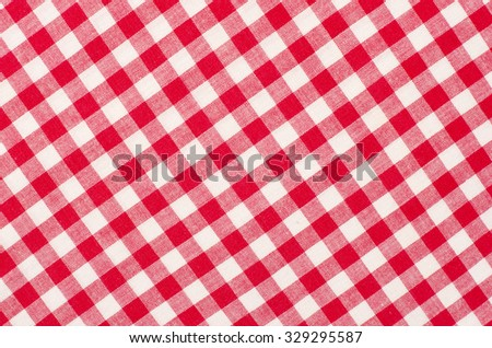 Close up on checkered tablecloth fabric. Red with white tartan square pattern as background. - stock photo