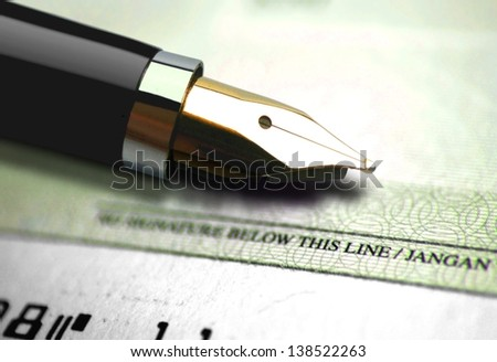Close up on cheque with an ink pen - stock photo